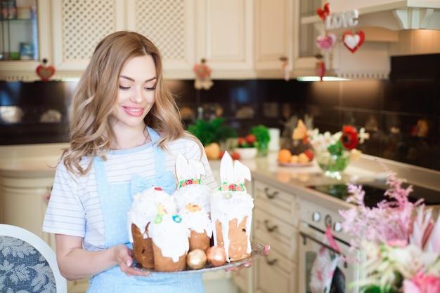 イースター、おめでとう。ケーキを持った母親がイースターの準備をします。