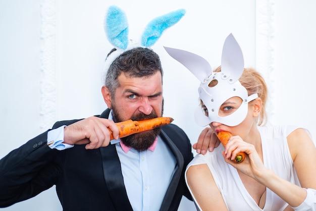 행복 한 부활절과 재미있는 부활절 날. 토끼 토끼 귀 의상. 놀란 된 토끼 커플 토끼 귀를 입고 당근을 먹는다.