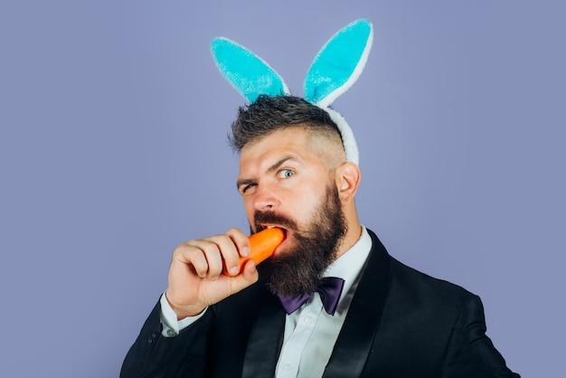 Счастливой пасхи и забавного пасхального дня. человек кролика кролика ест морковь. милый зайчик. празднование пасхи.