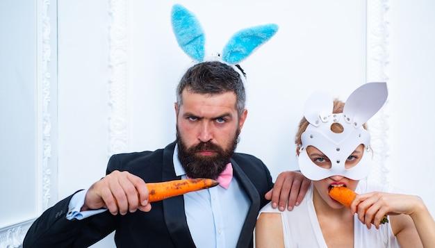 행복 한 부활절과 재미있는 부활절 날. 놀란 된 토끼 커플 토끼 귀를 입고 당근을 먹는다. 부활절 미소.