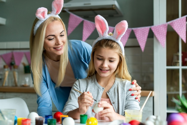 Happy easter atmosphere! funny, pretty mom making control, looking how her cute, small, joyful daughter draw, paint, decorate easter eggs, together wearing bunny ears