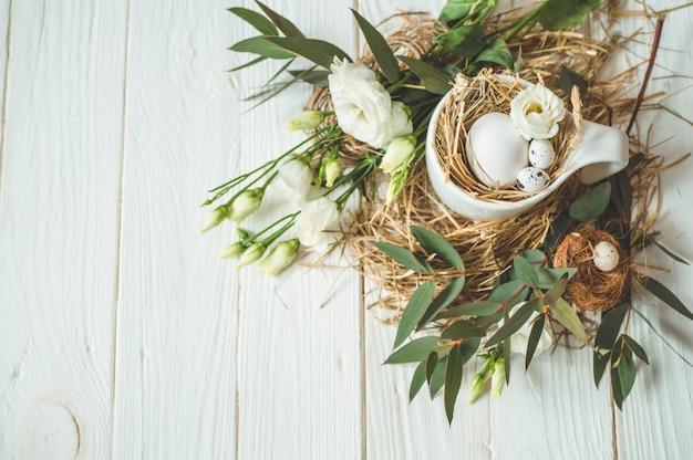 ハッピーイースターの背景。花飾り付きの木製の白い背景の上にカップのイースターエッグ。ハッピーイースターのコンセプト