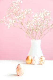 ハッピーイースターの背景。ピンクと金の卵とピンクの背景に白の咲くジプソギラ。優しい居心地の良い静物。