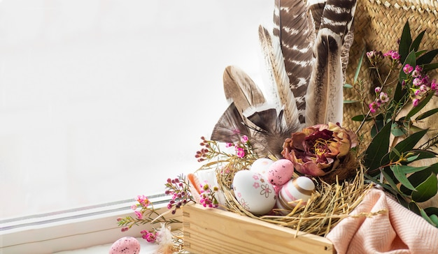 Happy easter background. pink easter eggs in a nest with floral decorations and feathers near the window
