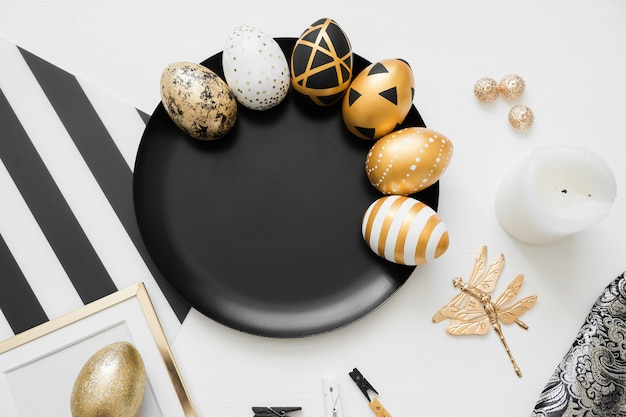 Happy easter background with golden decorated eggs on black plate