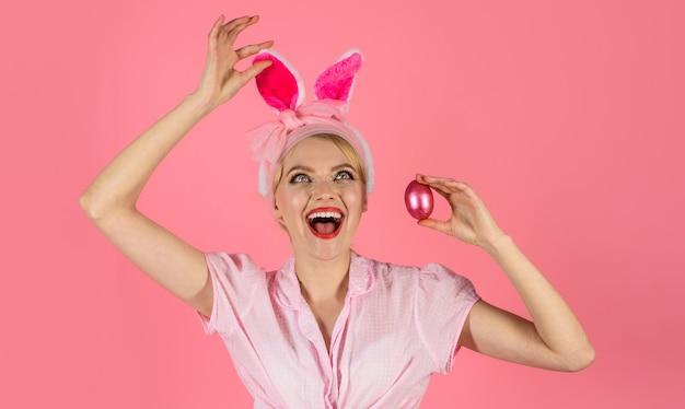 Счастливой пасхи. красивая молодая женщина с ушами зайчика и пасхальным яйцом. охотничьи яйца.