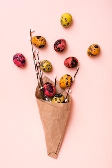 Хв. букет из крашеных перепелиных яиц и веток вербы, завернутых в коричневую бумагу на розовом фоне. вертикальный вид