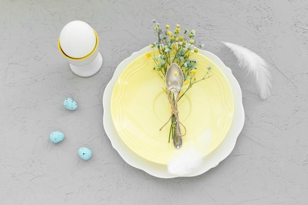 행복한 부활절 아침 또는 분기. 노란색 접시에 꽃과 함께 부활절 달걀입니다. 2021 년 최고의 회색과 밝은 노란색의 색상.
