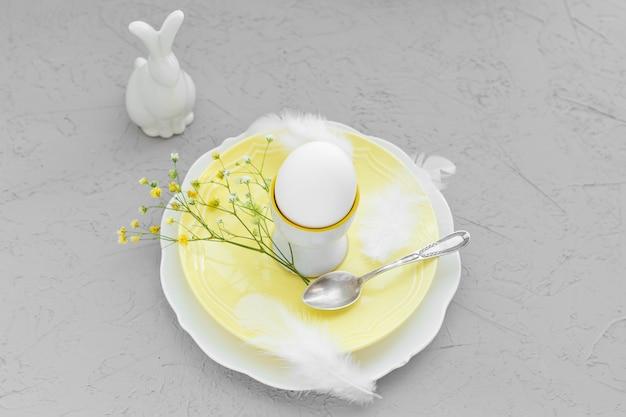 행복 한 부활절 아침 식사 또는 분기, 장식 및 라든지 꽃과 부활절 토끼 접시에 계란. 2021 년의 컬러로 구성한 궁극의 회색과 밝은 노란색.