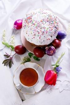 Счастливый натюрморт завтрака пасхи с белой фарфоровой чашкой чая, крашеными яйцами и свежеиспеченным куличом.