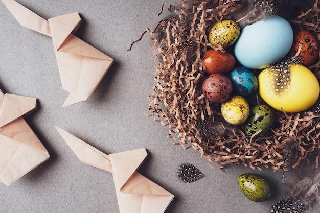 イースター、おめでとう。明るいお祝いのイースターの背景。上面図、フラットレイ。カラフルなイースターエッグ、ウサギの折り紙、灰色の背景の巣の羽、クローズアップ。