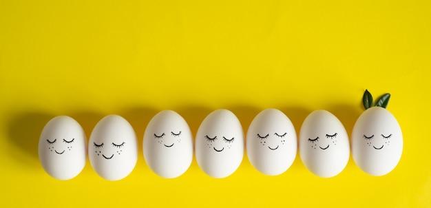 행복 한 부활절 카드. 봄에 그려진 얼굴로 귀여운 부활절 달걀 노란색에 나뭇잎