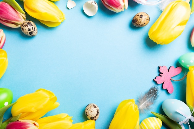 ハッピーイースターカード。青い表面にテキスト用のコピースペースがある黄色いチューリップとイースターウズラの卵のフレーム。上面図