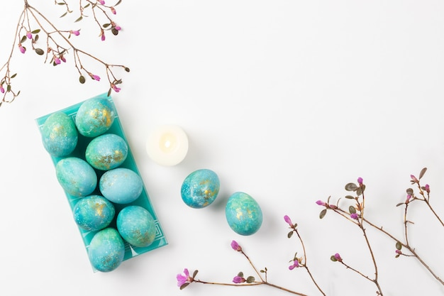 Happy easter card. stylish minimalistic composition of turquoise with gold easter eggs on a white background. candles and delicate spring flowers. flat lay, top view, copy space.