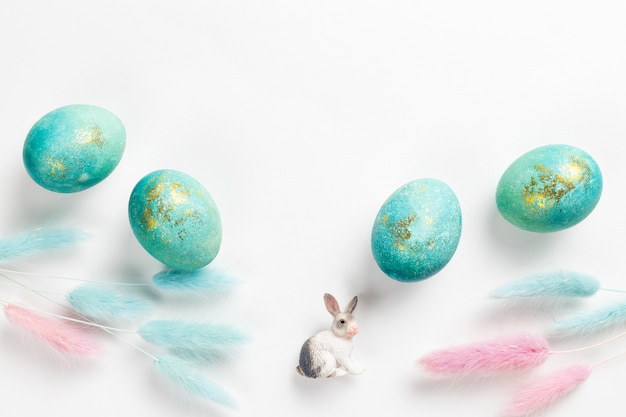 Happy easter card. stylish minimalistic composition of turquoise with gold easter eggs on a white background. figurine of a rabbit and delicate spring flowers. flat lay, top view, copy space