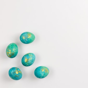 Happy easter card. stylish minimalistic composition of turquoise with gold easter eggs on a white background. flat lay, top view, copy space.