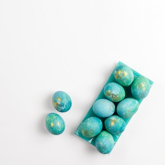 Happy easter card. stylish minimalistic composition of turquoise with gold easter eggs on a white background. flat lay, top view, copy space