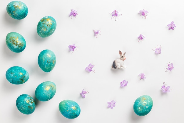 Happy easter card. stylish minimalistic composition of turquoise with gold easter eggs on a white surface. figurine of a rabbit and delicate spring flowers. flat lay, top view, copy space