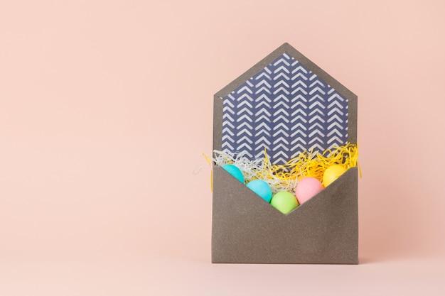 Счастливая пасхальная открытка с пасхальными яйцами в конверте на кремовых тонах.