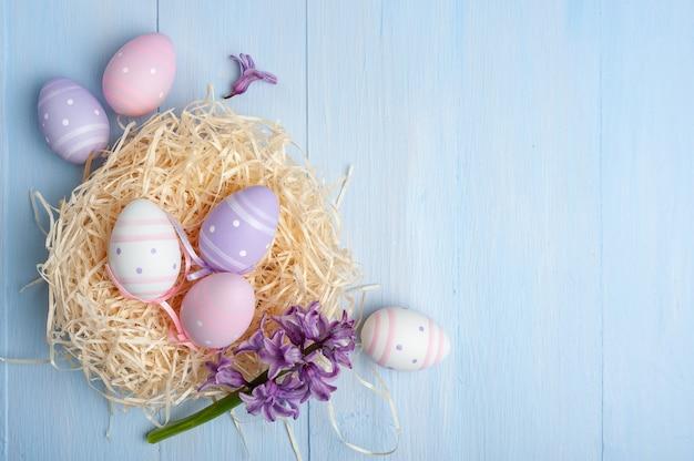 カラフルなテーブルに描かれた卵と花、あなたのカードの休日の背景と幸せなイースターカード。卵狩り、コピースペース