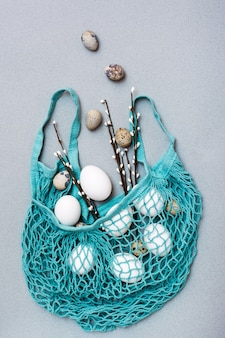 Хв. куриные и перепелиные яйца падают в синий сетчатый мешок с ветками вербы на сером фоне
