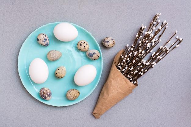 Хв. куриные и перепелиные яйца на тарелке и упаковка с ветвями вербы на сером фоне. вид сверху