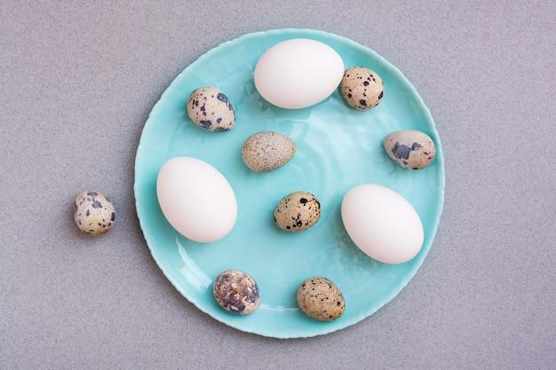 Хв. куриные и перепелиные яйца на тарелке на сером фоне. вид сверху