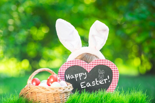 Happy easter! child bunny having fun outdoor. kid playing with eggs on green grass. spring holidays concept