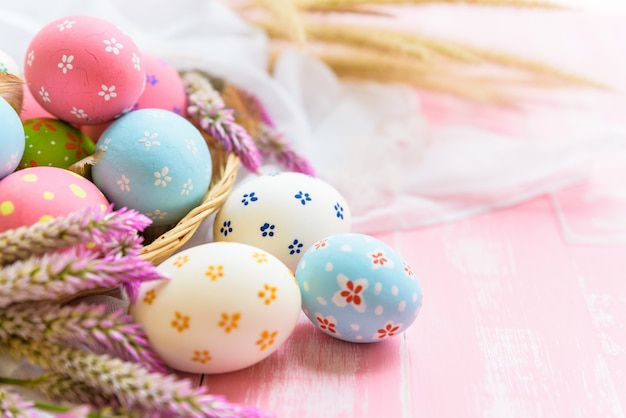 Happy easter! colorful of easter eggs in nest on pink and white wooden background.