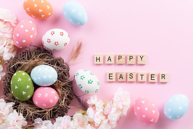 Happy easter! colorful of easter eggs in nest with flower and feather
