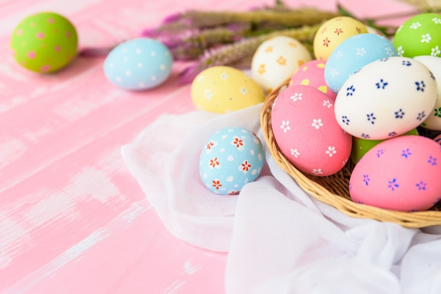 Happy easter! colorful of easter eggs in nest with flower on wooden background.