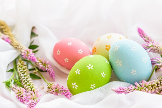 Happy easter! colorful of easter eggs in nest with flower.