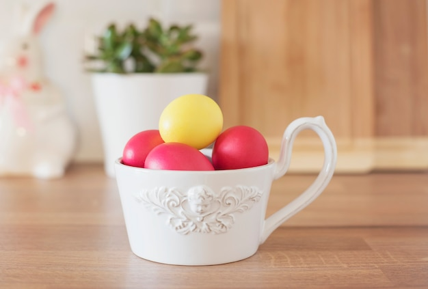 Happy easter! colorful easter eggs in white bowl, rabbit, succulent on the kitchen counter, close up. kitchenware in modern kitchen interior.