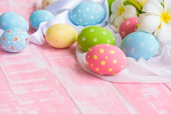 Happy easter! Colorful of Easter eggs in nest with flower on white cheesecloth wooden back
