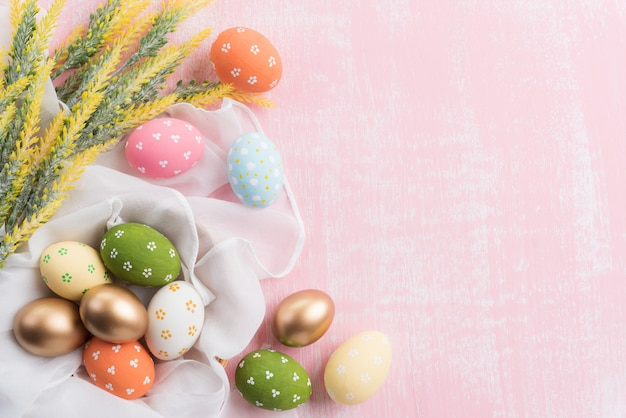 Happy easter! colourful of easter eggs in nest with flower on pink background.