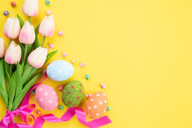 Happy easter! colourful of easter eggs in nest with pink tulip flower