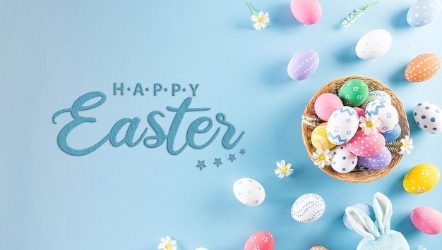 Счастливой пасхи красочные пасхальные яйца в гнезде с кроликом на пастельно-синем фоне