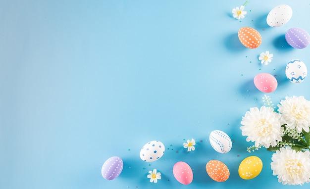 イースター、おめでとう!パステルブルーの花とイースターエッグのカラフル