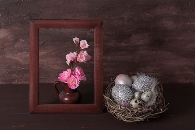Счастливая пасхальная композиция с розовыми цветами в рамке с гнездом и яйцами на коричневом фоне.