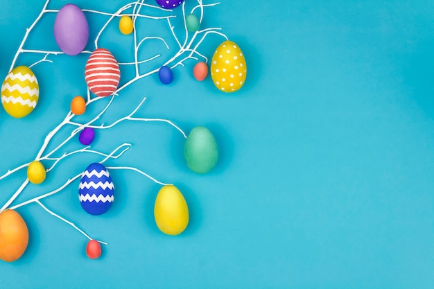 Happy easter concept. blue branch tree with colorful spring's flowers and colorful easter eggs on blue background
