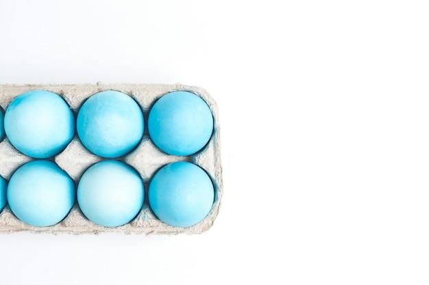 ハッピーイースターのコンセプト。卵コンパートメントに青い色で塗られた鶏卵。