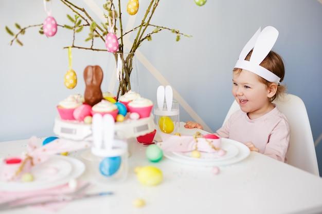 Концепция счастливой пасхи - милая маленькая девочка и украшенный стол с кексами, красочными крашеными яйцами и украшениями
