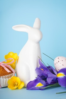 Счастливой пасхи концепции. кулич, пасхальный кролик и яйца с цветами на синем фоне.
