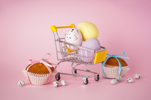 Happy easter concept. easter cake and easter eggs in a cart with flowers on a pink background.