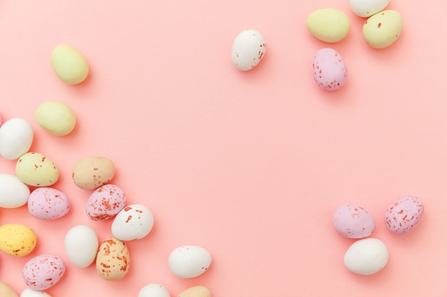 Happy easter concept. easter candy chocolate eggs and jellybean sweets isolated on trendy pastel pink background. simple minimalism flat lay top view copy space