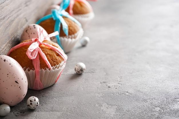 Счастливой пасхи концепции. пасхальные яйца и пасхальные кексы на серой поверхности, место для текста.