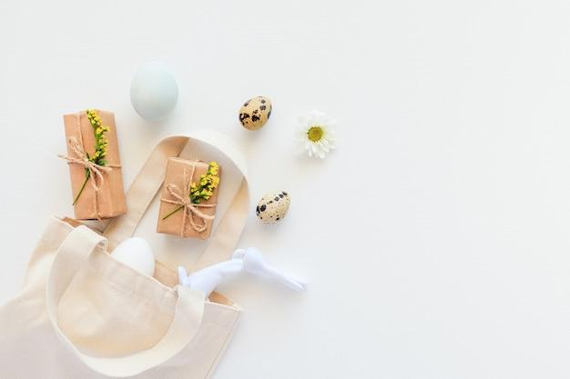 행복 한 부활절 개념입니다. 계란, 노란 꽃, 공예 선물 및 토끼 입상 흰색 배경에 섬유 가방을 날아