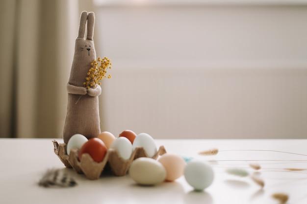 Счастливой пасхи концепция забавная игрушка кролик ручной работы и куриные яйца