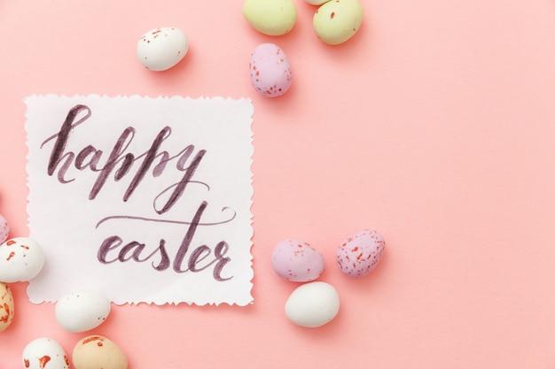 ハッピーイースターのコンセプトです。碑文ハッピーイースター文字キャンディチョコレートの卵とトレンディなパステルピンクの背景に分離されたジェリービーンズのお菓子。シンプルなミニマリズムフラットレイアウトトップビューコピースペース。