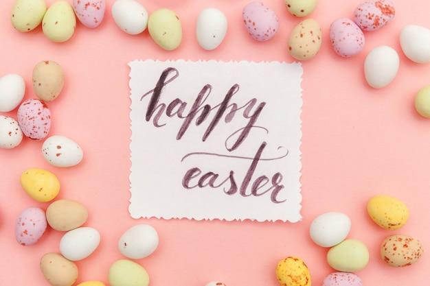 ハッピーイースターのコンセプトです。碑文ハッピーイースター文字キャンディチョコレートの卵とトレンディなパステルピンクの表面に分離されたジェリービーンズのお菓子。シンプルなミニマリズムフラットレイアウトトップビューコピースペース。